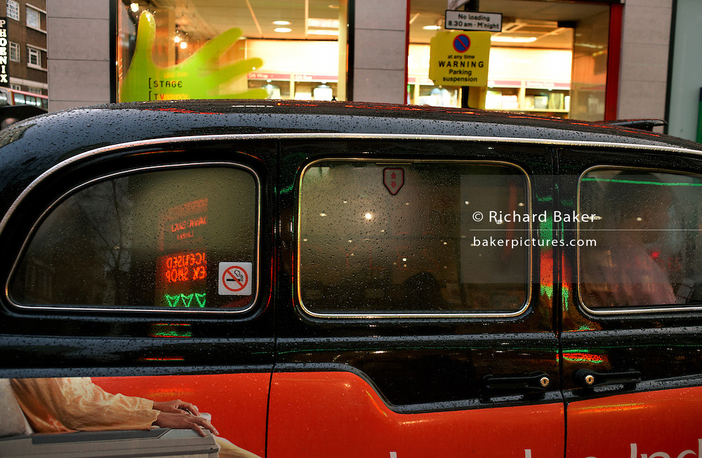 Just after heavy rain when the streets of London's West End are wet but brightening after the clouds have passed we look into the windows of a black taxi cab on the busy Charing Cross Road. It is a scene of urban transport and inclement weather. We can see the rough form of the taxi driver at the front of his vehicle but it appears that he is stationary, possibly awaiting for the return of his fare-paying passenger from nearby bookshops such as Foyles in the background. A No-Smoking sticker is on the window and advertising on the side panel shows the arms of an airline passenger sitting in an airliner seat but once the taxi passenger returns, their head will be directly above this. The car's roof is still wet from rain, glistening in the artificial street lights that have turned on during the dark rain storm.