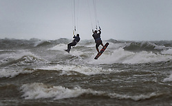 © Licensed to London News Pictures. 30/07/2021. Lancing, UK. A pair of kite surfers make use of the high winds at Lancing in West Sussex. Parts of the south are feeling the effects of Storm Evert, the first named storm of summer 2021. Photo credit: Peter Macdiarmid/LNP