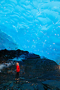A hiker in an ice cave in Mendenhall Glacier, Juneau, Alaska.