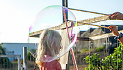 Young girl makes a large soap bubble while other excited children watch and wait their turn