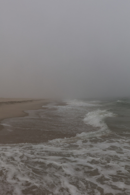 Waves washing towards the shore of Surfside on a foggy summer afternoon.
