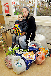 © Licensed to London News Pictures. 12/12/2013; Bristol, UK.  Kelly Harris age 34 from Lawrence Weston with her son Alex Britton age 4 collects a weeks worth of supplies for herself, Alex and three other children at Bristol North West Food Bank distribution point at Lawrence Weston Baptist Church.  This is only Kelly's second visit to the food bank this year.  A wide range of people use the service, both those on benefits and those in work, and from a wide range of backgrounds.  Ffi: bristolnwfoodbank.org.uk  12 December 2013.<br /> Photo credit : Simon Chapman/LNP