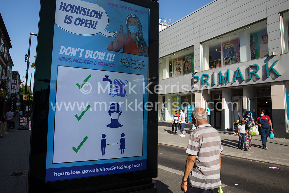 London, UK. 17th July, 2021. A member of the public passes a London Borough of Hounslow Covid-19 public information sign urging residents to take precautions to minimise the spread of the coronavirus amid rising concern regarding the Delta variant. The UK government is currently still expected to lift almost all restrictions on social contact on 19th July, known as 'Freedom Day', but the current wave driven by the Delta variant is not expected to peak until mid-August.
