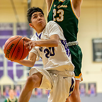 Photo: Jeffery Jones<br /> <br /> Miyamura Patriot Mathias Rodriguez (20) jumps as he tries to score a basket against Los Alamos Hilltopper Harrison Frank (23) during Saturday afternoon's game in Gallup.