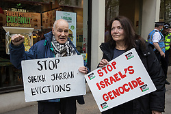 London, UK. 11th May, 2021. Pro-Palestinian activist Eric Levy (l), 92, and a fellow activist hold signs during a protest outside the UK headquarters of Elbit Systems, an Israel-based company developing technologies used for military applications including drones, precision guidance, surveillance and intruder-detection systems. The activists were protesting against the company's presence in the UK and in solidarity with the Palestinian people following attempts at forced evictions of Palestinian families in the Sheikh Jarrah neighbourhood of East Jerusalem, the deployment of Israeli forces against worshippers at the Al-Aqsa mosque during Ramadan and air strikes on Gaza which have killed several children.
