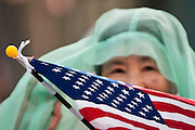 An older Asian woman peers over an American flag while participating in a parade in Waikiki.