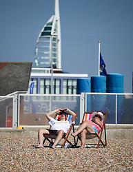 © Licensed to London News Pictures. 21/06/2014. Southsea, Hampshire, UK. A couple sitting in deck chairs sunbathing in the sunny weather by the seaside in Southsea, Hampshire today (21st June 2014). The weather in the UK over the weekend is set to be warm and sunny. Photo credit : Rob Arnold/LNP