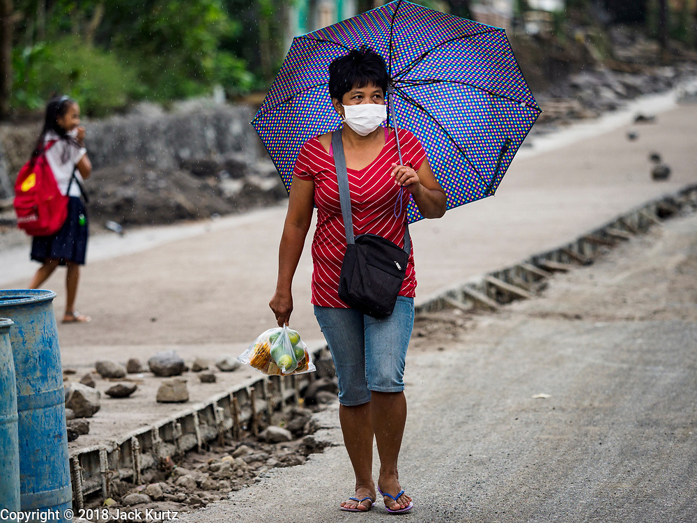 """22 JANUARY 2018 - GUINOBATAN, ALBAY, PHILIPPINES:  A woman in Guinobatan wears a face mask while she walks home from shopping. Several communities in Guinobatan were hit ash falls from the eruptions of the Mayon volcano and many people wore face masks to protect themselves from the ash. There were a series of eruptions on the Mayon volcano near Legazpi Monday. The eruptions started Sunday night and continued through the day. At about midday the volcano sent a plume of ash and smoke towering over Camalig, the largest municipality near the volcano. The Philippine Institute of Volcanology and Seismology (PHIVOLCS) extended the six kilometer danger zone to eight kilometers and raised the alert level from three to four. This is the first time the alert level has been at four since 2009. A level four alert means a """"Hazardous Eruption is Imminent"""" and there is """"intense unrest"""" in the volcano. The Mayon volcano is the most active volcano in the Philippines. Sunday and Monday's eruptions caused ash falls in several communities but there were no known injuries.   PHOTO BY JACK KURTZ"""