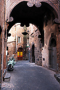 Scooter and doorways in an alley in Orvieto, Italy.