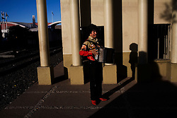A musician plays his accordion in downtown Nogales, waiting for someone to hire him.