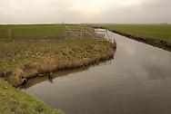 Buitendijks kweldergebied van waterschap Blija Buitendijks.<br /> Waterschap Blija Buitendijks is het kleinste waterschap van Nederland. Het waterschap beheert 100 hectare weiland, gelegen bij het dorp Blija in het noorden van Friesland, tussen de Waddenzeedijk en zomerdijk. Direct achter de 2,25 m +NAP hoge zomerdijk (links op de foto) bevindt zich het uitgestrekte kweldergebied van de Waddenzee. Bij hoogwater (vloed) stroomt het buiten de zomerdijk gelegen kwelder regelmatig onder water. Bij extreem hoog water, bijvoorbeeld bij springtij en noordwesterstorm komt het zeewater vanuit de Waddenzee ook over de zomerdijk. De door het waterschap beheerde polder komt dan geheel onder water te staan, soms zelfs tot halverwege de Waddenzeedijk. Bij afgaand tij (eb) stroomt het zeewater via de klepstuwen in de zomerdijk terug naar de Waddenzee. De afgebeelde watergang (afwateringssloot) bevindt zich langs de zomerdijk met daarin de betonnen duiker met klepstuw.