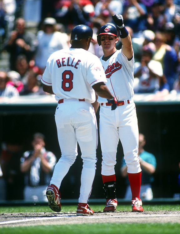 CLEVELAND - 1995:  Jim Thome #25 greets Albert Belle #8 of the Cleveland Indians after Belle hit a home run in an MLB game at Jacobs Field in Cleveland, Ohio.  Thome played for the Indians from 1991-2002.  Belle played for the Indians from 1989-1996.  (Photo by Ron Vesely)