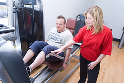 Fitness instructor showing young man how to use the leg press machine at his sports leisure centre,