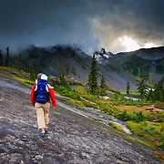 Heather Goodrich hikes along the lava beds with her new born son Micah at sunset during a clearing rain storm in North Cascades National Park, Washington.