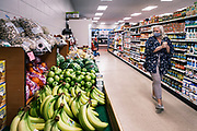 "03 AUGUST 2020 - JEWELL, IOWA:  A shopper looks at produce in the Jewell Market. The only grocery store in Jewell, a small community in central Iowa, closed in 2019. It served four communities within a 20 mile radius of Jewell. Some of the town's residents created a cooperative to reopen the store. They sold shares to the co-op and  held fundraisers through the spring. Organizers raised about $225,000 and bought the store, which had its ""soft opening"" July 8. The store celebrated its official reopening Monday August 3. Before the reopening, Jewell had been a ""food desert"" for seven months. The USDA defines rural food deserts as having at least 500 people in a census tract living 10 miles from a large grocery store or supermarket. There is a convenience store in Jewell, but it sells mostly heavily processed, unhealthy snack foods that are high in fat, sugar, and salt.       PHOTO BY JACK KURTZ"