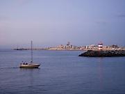 Zeilboot vaart de haven van Sceheveningen binnen. Havenhoofd, Scheveningen, Den Haag. - Sailing boat navigates to the harbour of Scheveningen. Pier, Scheveningen, The Hague, Netherlands