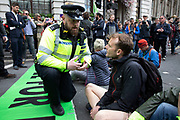 Climate change activists from the Extinction Rebellion group are cautioned by police before being arrested for blocking the street at Bank in the heart of the City of London financial district in protest that the government is not doing enough to avoid catastrophic climate change and to demand the government take radical action to save the planet, on 25th April 2019 in London, England, United Kingdom. Extinction Rebellion is a climate change group started in 2018 and has gained a huge following of people committed to peaceful protests.
