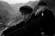 Two Hmong men take a break along the mountainous roadside as they make their way to a funeral, Ha Giang Province, Vietnam, Southeast Asia