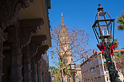 Ribbons decorate the old gas lamps outside the historic Dock Street Theatre with St. Philips Church steeple<br /> during Christmas in Charleston, SC.