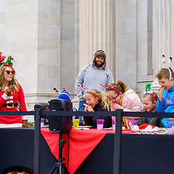 Gettysburg, PA / USA - December 7, 2019:  Children participate in Christmas Cookie eating contest on the steps of the public library in the downtown during the annual Christmas Festival.