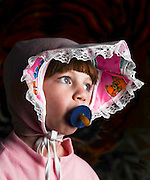 Young girl of 6 dressed up as a baby with pacifier in her mouth