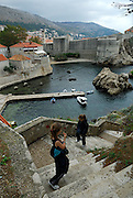 Elevated view of two children (9 years old and 5 years old) ascending steps to Fortress Lovrinjenac (Fort of Saint Lawrence), with Dubrovnik's oldest harbour, Kalarinja, Dubrovnik old town and Fortress Bokar in background. Dubrovnik, Croatia