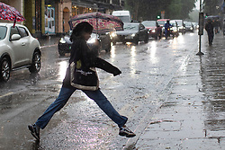 © Licensed to London News Pictures. 25/07/2021. London, UK. A person jumps over a large puddle during a thunderstorm in Greenwich Town Centre in South East London . An amber weather warning for thunderstorms is in place in parts of London and the South East . Photo credit: George Cracknell Wright/LNP