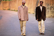 Two young Xhosa, who have recently become men by going through the traditional Xhosa male initiation rite, are going for a walk in Khayalethu South Township, Knysna, South Africa, in December, 2006. As signs of their manhood they are wearing red facial paint, long trousers, a shirt, a jacket and a cap, and, following local customs, they will continue to do so for about six months.