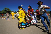 An Apache girl, dressed in buckskin dress, runs during her Sunrise Dance, a first menstruation rite, the San Carlos Apache Reservation, Arizona, USA. She runs four times, each time a little bit longer. This symbolises the four stages of life. Close behind her godmother and relatives  follow, the women dressed in camp dresses. The food, snacks and drinks on the ground symbolise a life without material want. The Sunrise Dance is supposed to prepare the girl for adulthood and to give her a long and healthy life. The ceremony is also an enactment of the Apache creation myth and during the rites the girl 'becomes' Changing Woman, a mythical female figure, and comes into possession of her healing powers.