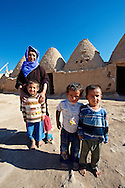 """Pictures of the beehive adobe buildings of Harran, south west Anatolia, Turkey.  Harran was a major ancient city in Upper Mesopotamia whose site is near the modern village of Altınbaşak, Turkey, 24 miles (44 kilometers) southeast of Şanlıurfa. The location is in a district of Şanlıurfa Province that is also named """"Harran"""". Harran is famous for its traditional 'beehive' adobe houses, constructed entirely without wood. The design of these makes them cool inside. 29 .<br /> <br /> If you prefer to buy from our ALAMY PHOTO LIBRARY  Collection visit : https://www.alamy.com/portfolio/paul-williams-funkystock/harran.html<br /> <br /> Visit our TURKEY PHOTO COLLECTIONS for more photos to download or buy as wall art prints https://funkystock.photoshelter.com/gallery-collection/3f-Pictures-of-Turkey-Turkey-Photos-Images-Fotos/C0000U.hJWkZxAbg ."""