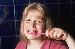 Young girl brushing teeth in bathroom with red toothbrush,