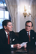 President Ronald Reagan reads a statement in the Cabinet Room of the White House which Vice President H.W. Bush looks on.  Date April 1984<br />Photo by Dennis Brack