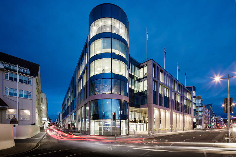 Corporate offices lit up at night in the offshore finance and business district of St Helier, Jersey, Channel Islands