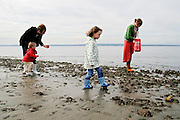 Brooke and Seth Patterson, together with their two children Phinaeus and Madison (center) look for seashells at Golden Gardens beach in Seattle, Washington on April 4, 2007.