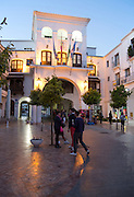Flags flying on town hall Ayuntamiento building at night, Nerja, Malaga province, Spain