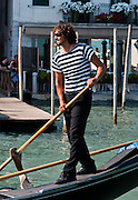 """Gondolier. Gondolas are traditional, flat-bottomed rowing boats which ferry people through Venetian canals. From a peak of 10,000 gondolas 200 years ago, just 500 gondolas now serve Venice. The banana-shaped modern gondola was developed in the 1800s. The left side of the gondola is made longer than the right side to resist leftwards drift at the forward stroke. The gondolier stands on the stern facing the bow and rows just on the right side, with a forward stroke and compensating backward stroke. The oar or rèmo is held in an oar lock, or fórcola, shaped for several rowing positions. The decorative fèrro (meaning iron) ornament on the front can be made of brass, stainless steel, or aluminum, as counterweight for the gondolier standing near the stern. The six horizontal lines and curved top of the ferro represent Venice's six sestieri (districts) and the Doge's cap. Painting gondolas black originated as a sumptuary law eliminating ostentatious competition between nobles. Until the early 1900s, many gondolas had a small cabin (felze) with windows which could be closed with louvered shutters--the original """"venetian blinds."""" The romantic """"City of Canals"""" stretches across 117 small islands in the marshy Venetian Lagoon along the Adriatic Sea in northeast Italy, Europe. Venice and the Venetian Lagoon are honored on UNESCO's World Heritage List. For licensing options, please inquire."""