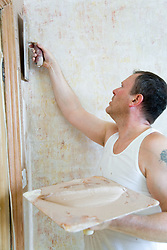 Man using a hawk and trowel to plaster a wall,