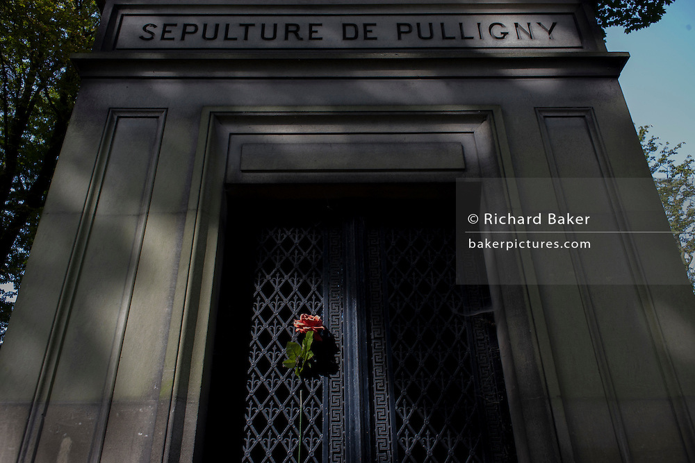 Single red rose attached to the gates of the mausoleum for the Pulligny family in the Pere Lachaise cemetery, Paris.