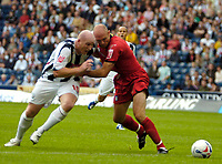 Photo: Ed Godden.<br />West Bromwich Albion v Colchester United. Coca Cola Championship. 19/08/2006. John Hartson (L) is brought down by Wayne Brown (R) to give Albion a penalty.