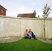 Emma and Martin are a young professional couple living in the experimental community village of Poundbury, Dorset, England. Sitting in their landscaped rear garden the married couple have their portrait taken against a high concrete wall that serves as their property's back boundary. The roofs of neighbouring homes appear over this partition and young tree saplings are fastened to a stake. Poundbury is the visionary model village that the Charles, Prince of Wales sought to develop in 1993 as a successful and pioneering town near Dorchester, built on land owned by his own Duchy of Cornwall, challenging otherwise poor post-war trends in town planning and to some extent following the New Urbanism concept from the US except that the design influences are European.