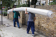 Two delivery workmen carry a heavy roll of carpet along a south London street. Having offloaded their load from a nearby lorry (truck) the work colleagues haul the carpet over the left shoulders and continue down this quiet suburban street towards an address on the right. By balancing the weight and making the centre of gravity in the middle to ease their effort, the men still struggle to make their way on the pavement.