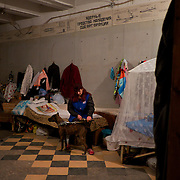 DONETSK, UKRAINE - OCTOBER 18, 2014: A couple of Ukrainian IDPs mind their pet dog at a bomb shelter in Petrovskiy district, Donetsk.More than one hundred people have been living for the past four months at the shelter. Many had their homes destroyed during fighting between DNR combatants and the Ukrainian National Guard. CREDIT: Paulo Nunes dos Santos