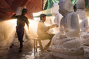 Buddha statue makers work in the dust of a Mandalay marble workshop as sun rays pour inside, Tuesday, October 29, 2015.