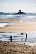 Family enjoying a healthy outdoor lifestyle, walking on the beach by La Rocco Tower at St Ouen's Bay in winter sunshine