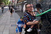 Woman and children holding long sword shaped balloons on 10th August 2021 in London, United Kingdom.