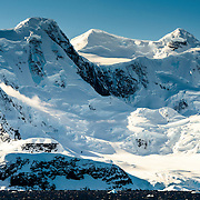 Dramatic snow and ice-covered mountains rise up from the shoreline of the Gerlacht Strait on the western coast of the Antarctic Peninsula.