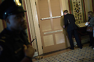 """An aide peeks in the committee room door as Democratic members of the 'super committee' wrap up a meeting at the U.S. Capitol in Washington. With a deadline less than a week away, members of a 12-member """"super committee"""" tasked with finding $1.2 trillion in budget savings confronted the same barriers that have thwarted earlier efforts to rein in the growing national debt."""