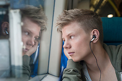 Boy listening music on headphones and looking out of window in train, London, England