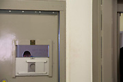 """A view of a male prisoner through the peephole window of a cell door in the Healthcare Wing of HMP Pentonville, London, UK. An offender has written """"Happy Birthday To Me"""" on the white wall in the cell.   HM Prison Pentonville is an English Category B men's prison, operated by Her Majesty's Prison Service. Pentonville Prison is located on  Caledonian Road in the Barnsbury area of the London Borough of Islington, north London, United Kingdom. (Photo by Andy Aitchison)"""