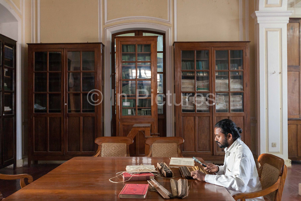 Mr Thrukumaran a researcher studies ancient palm leaf manuscripts in the library of the Department of Indology at the French Institute, Pondicherry, India. the French Institute of Pondicherry has a collection of 8,600 Hindu religious manuscripts and similar records and forms part of India's National Mission for Manuscripts.